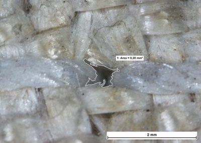 Przykładowy rozmiar otworów wraz z nicią - tkanina szklana